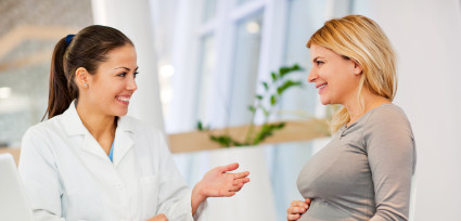 Female doctor talking to a pregnant woman.