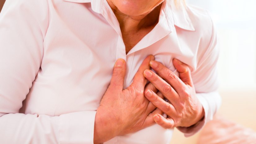 Old woman holding breast because of heart infarction